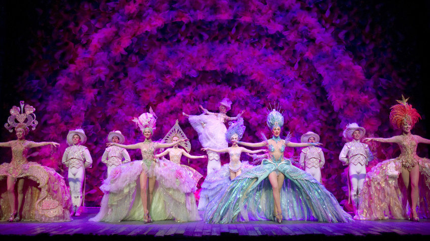 Picture of Loveland sequence from 2011 Broadway production - front row girls in follies costume with chorus line at back. Fluffy pink and purple clouds behind