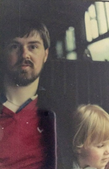 80s photograph of Sarah's dad wearing a red tshirt and jacket, looking young, with a beard. Sarah is 3 or 4 with very blonde hair, they are on a bus?